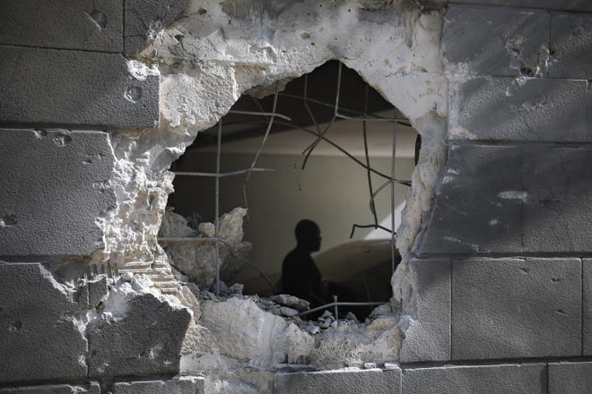 A man is seen trough a hole in a wall of a residential building Friday after it was struck by a rocket fired from the Gaza Strip in Ashkelon, Israel.