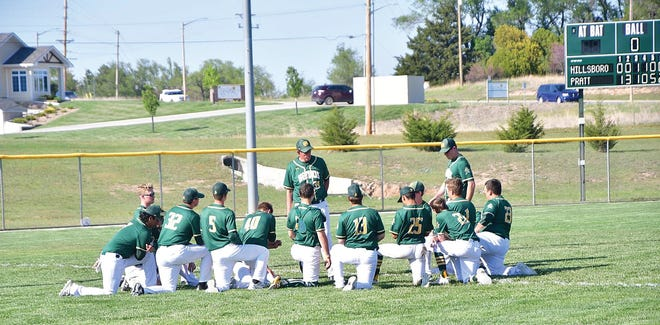 The Pratt High School baseball team meets with Coach Hill after a successful game against Hillsboro last Friday. The Greenbacks won both ends of the double-header and move on towards post-season action next week.