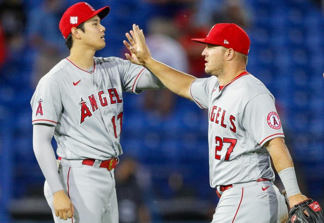Apr 9, 2021; Dunedin, Florida, CAN;  Los Angeles Angels designated hitter Shohei Ohtani (17) (left)  center fielder Mike Trout (27) (center) and left fielder Justin Upton (10) celebrate after beating the Toronto Blue Jays 7-1 at TD Ballpark. Mandatory Credit: Nathan Ray Seebeck-USA TODAY Sports