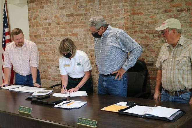 Mark Twain National Forest's Supervisor, Sherri Schwenke, signing Crane Lake decision at Iron County Commissioners meeting. (left to right:  Ben Young, Sherri Schwenke, Jim Scaggs, and Ronnie Chandler)