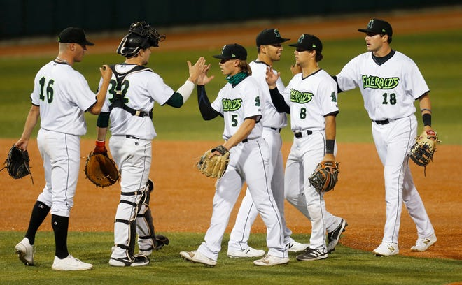 Eugene Emeralds players celebrate their win over the Hillsboro Hops in their first home game of the 2021 season at PK Park in Eugene.