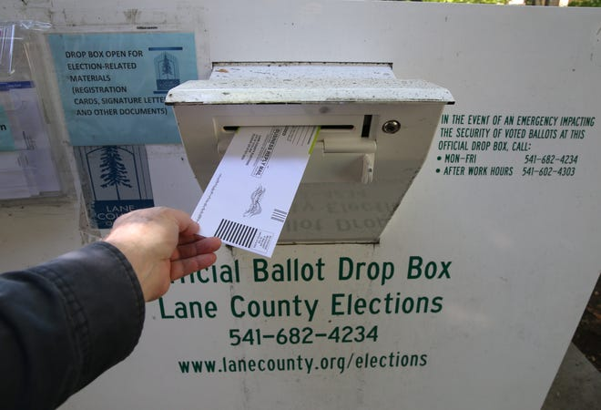 A ballot goes into an official ballot box at the Lane County Election building in Eugene.