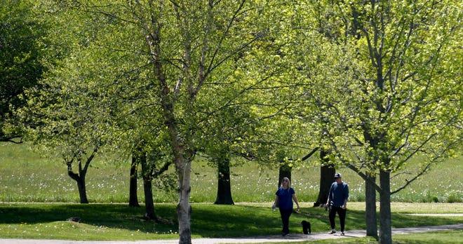 People enjoy a walk through Metzger Park in Louisville.