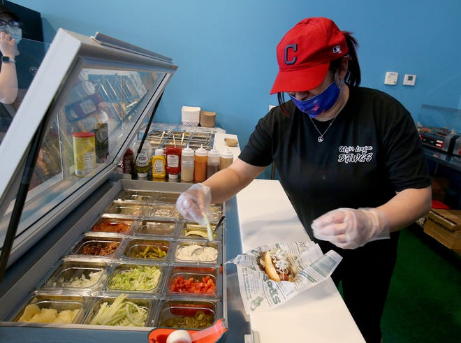 Major League Dawgs employee Sana Sousa adds toppings to an all-beef hot dog at the new gourmet hot dog shop at 6817 Wales Ave. NW. The restaurant is in the same plaza as a new Hartville Hometown Meats and Seafood Company location.