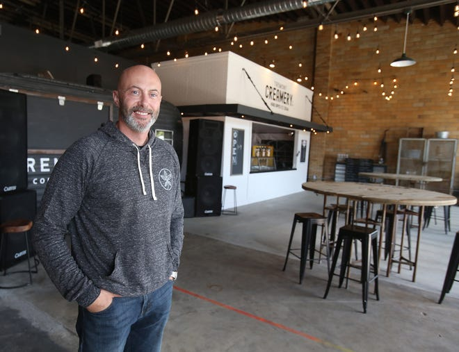 Tremont Creamery owner Jason Lamp is pictured Friday inside of his new business at 225 Erie St. N, Massillon. The creamery is adjacent to Tremont Coffee Co. It has 22 flavors of ice cream and a half-dozen parfait varieties.