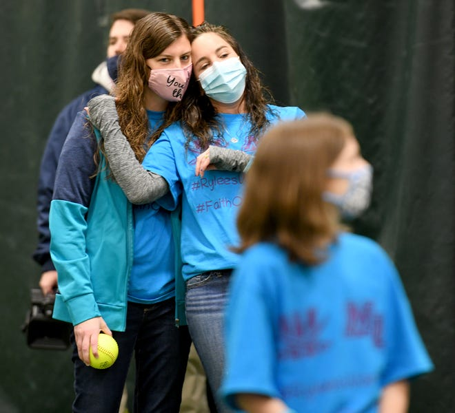 Lindsey Abbuhl (rear left) is comforted at a softball event in February for her daughter, Rylee, in the foreground.