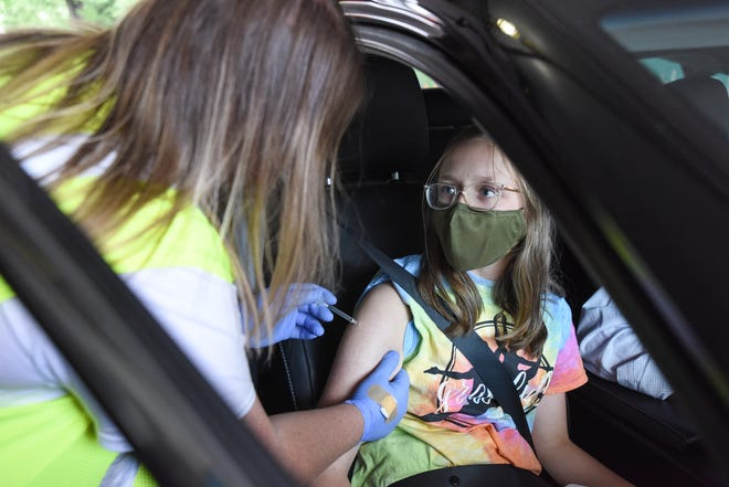 Abigail Isaac gets her fist dose of COVID-19 vaccine this week at a drive-thru vaccination clinic at Atrium Health Carolinas Medical Center, in Charlotte, on May 13, 2021.