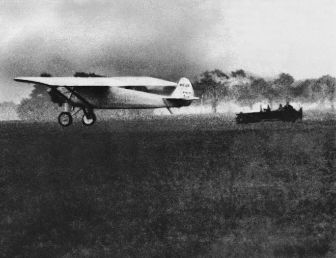 """Charles Lindbergh flies """"The Spirit of St. Louis"""" out of Roosevelt Field in New York on May 20, 1927, as he begins his flight to Paris to be the first to complete a non-stop transcontinental flight."""
