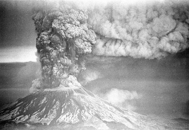 In this May 18, 1980, photo, Mount St. Helens sends a plume of ash, smoke and debris skyward as it erupts. The eruption killed more than 50 people and blasted more than 1,300 feet off the mountain's peak.