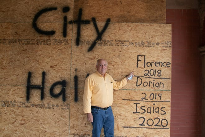 New Bern Mayor Dana Outlaw stands beside a boarded up City Hall as Hurricane Isaias approaches in 2020.