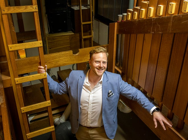Organist Wesley Hall inside the the pipe organ at First Baptist Church.