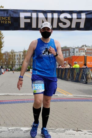 The finish line at the 2021 Providence Marathon is behind Dan Foley, who completed 40 marathons before he turned 40.