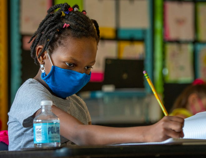 Benedicta Akomea writes an essay in her second-grade class at Chandler Elementary Community School May 14.