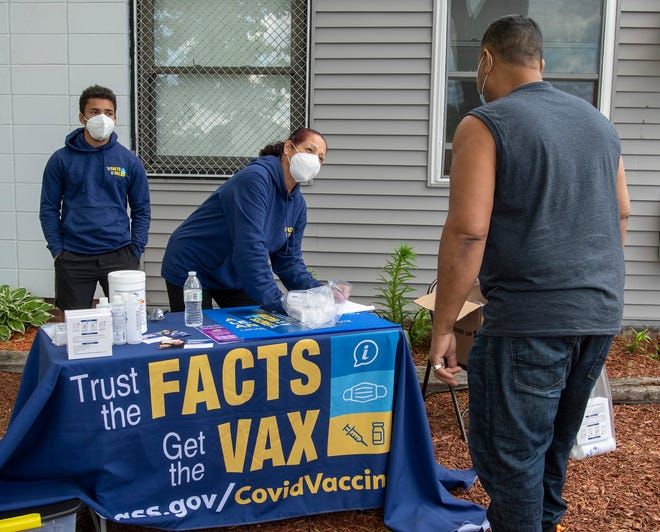 Fabian Valencia, left, and Maria Siemaszko, distribute vaccine information, masks and sanitizer to people outside Friendly House in Worcester on Friday.