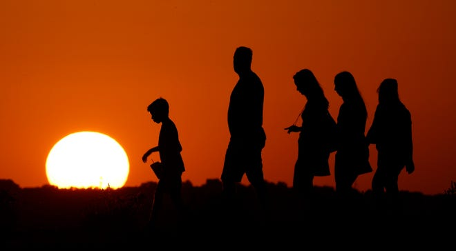 The sun sets beyond people on a 100-degree day.