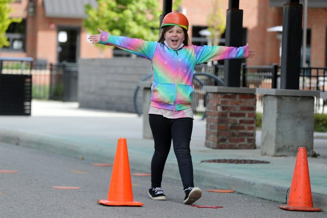 Aliza Grenier, 9, of Hilliard crosses the finish line of a bicycle course while balancing objects on her head at Hilliard's Station Park during the Wheels and Waffles event May 8. The event included waffles from Coffee Connections of Hilliard, live music and bicycle safety inspections.
