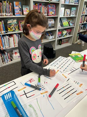 Stevenson Elementary School first-grader Audrey Ward uses Ozobots (little robots) to create artwork. Students use the markers to draw a code. Then the Ozobots scan the colors from the markers and move based on what colors the students choose.