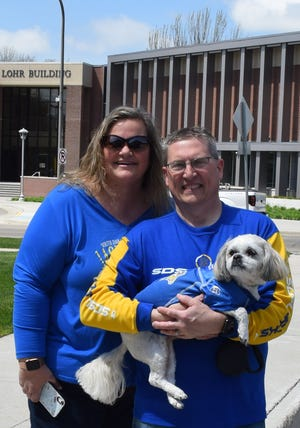 Kim, left, and John Vig showed up with their furry fan Cooper in SDSU attire to wish the team goodluck during Friday's send-off parade.