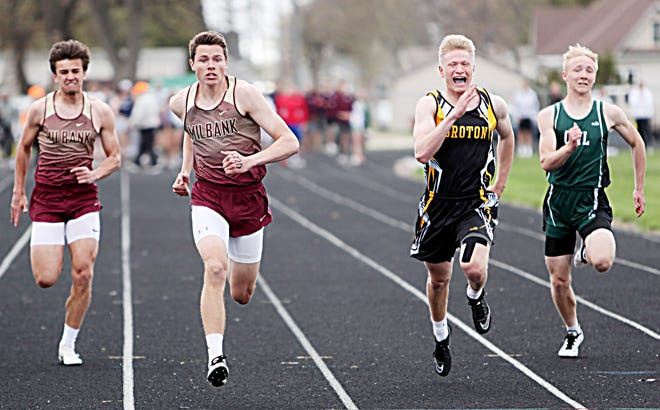Bennett Schwenn of Milbank Area, second from left, sprints to victory in the Northeast Conference track and field meet at Groton. Also pictured, from left, are Sawyer Gauer of Milbank Area, Andrew Marzahn of Groton Area and Trey Huber of Clark-Willow Lake. Schwenn won four events and Milbank Area swept the team titles in the meet.
