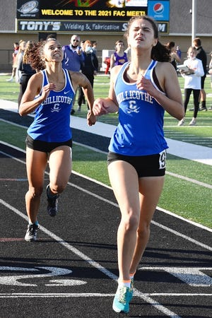 Chillicothe sisters Simone and Danielle Fluerima cross the finish line of the girls 1600-meter run at the Frontier Track Championships at Miami Trace High School on May 14, 2021. The Chillicothe boys would get first place overall and the girls second.