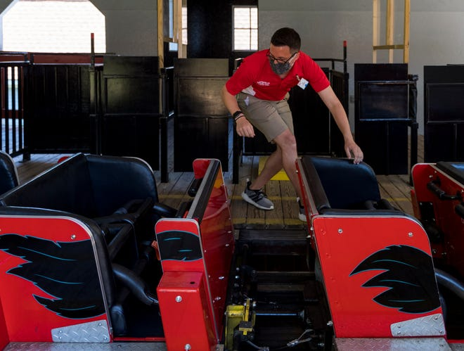 Holiday World ride operator Ty Kunkel checks the safety restraint on each cart of The Raven roller coaster train Friday morning, May 14, 2021.