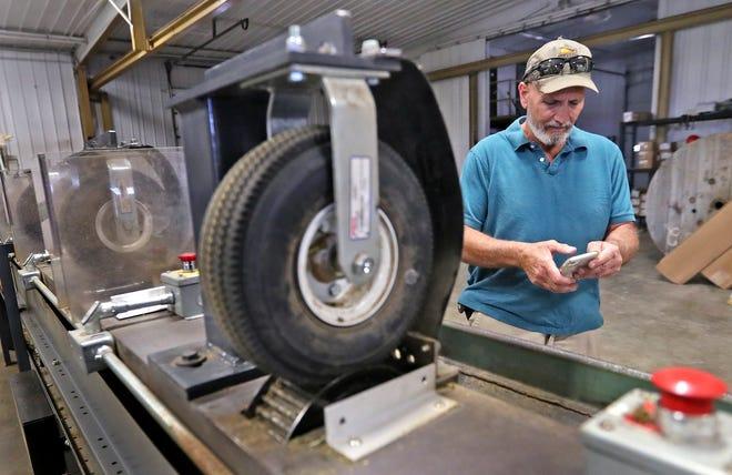 Mark Davidson spricht über seinen Hanfanbau, während er am Donnerstag, dem 13. Mai 2021, in seiner Hanfanlage Heritage Farmacy in Crawfordsville steht.  Die zur Verarbeitung des Hanfs verwendeten Maschinen wurden nach den von Davidson und seinen beiden Partnern abgeleiteten Konzepten von Grund auf neu gebaut.  Die hier links gezeigte Maschine ist ein Fünf-Mann-Bucker.  Die Stiele werden in kleine Löcher in dieser Maschine eingesetzt und entfernt.  Das Produkt fällt dann auf das darunter liegende Förderband.