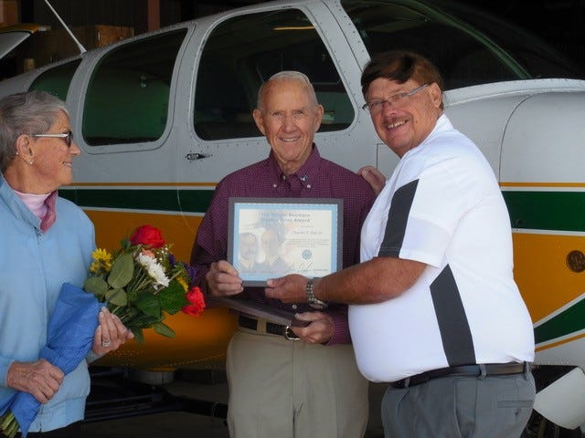 Daniel M. Keen, right, retired Aviation Safety Inspector for the Federal Aviation Administration, presents Charles T. Dye Jr., center, of West Lafayette, Ind., with the Wright Brothers Master Pilot Award as Dye's wife, Mary Ann, looks on.