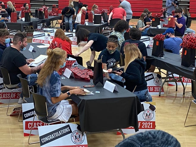 A group of students pull out their commitment papers to sign during the Prexie Signing Day at Harding High School Friday, May 14, 2021. The event celebrates seniors who are going off to college, the military, or the workforce.