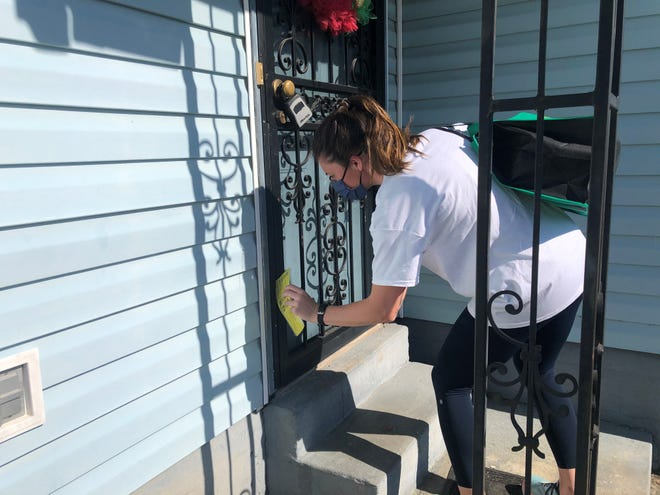 Tricia Murphy distributes materials about the COVID-19 vaccine to a home in 38106 May 15, 2021.