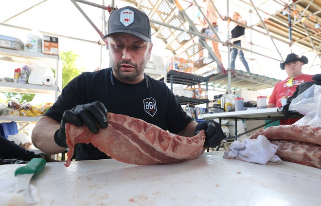 James Cruse works to cut the fat from a rack of pork ribs for the best rib contest at the WCBCC at Tom Lee Park on Friday, May 14, 2021.