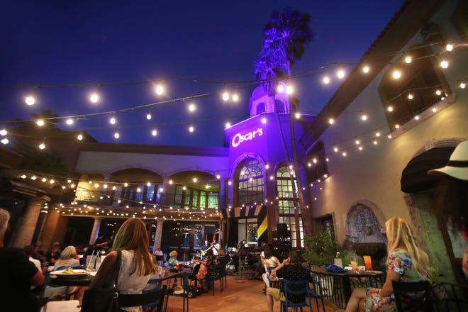 Patrons sit under strings of lights in the outdoor courtyard of Oscar's in downtown Palm Springs, Calif., on May 13, 2021. Oscar's will be holding its first T-Dance since the pandemic this Sunday. The event for prescreened, fully vaccinated attendees is sold out.
