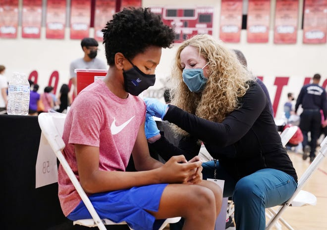 Hunter Sansone, age 13, receives his shot from Dr. Cara Christ of the Arizona Department of Health Service at Arizona's first COVID-19 vaccination site for underserved youths ages 12 to 15 at C.O. Greenfield Elementary School in Phoenix on May 13, 2021.