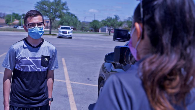 Christian Martinez, age 15 at far left, is interviewed by local media after receiving the COVID-19 vaccine at the Shannon Medical Center clinic at the Sunset Mall on Thursday, May 13, 2021.