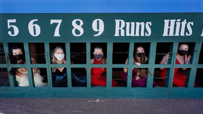 While wearing their prom gowns, students peer through the scoreboard at the New Hampshire Fisher Cats minor league baseball stadium in Manchester, N.H., on Monday, April 26, 2021. After a year without proms, school districts across the country are debating whether they can safely hold an event that many seniors consider a capstone to their high school experience. The nearly 300 student senior class of Manchester's Central High School are waiting to get approval from the city's board of health so they can have their prom at the outdoor venue, due to COVID-19 concerns.