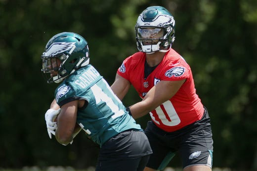 Philadelphia Eagles quarterback Jamie Newman, right, hands the ball off to running back Kenneth Gainwell during rookie minicamp at the NFL football team's training facility, Friday, May 14, 2021, in Philadelphia.