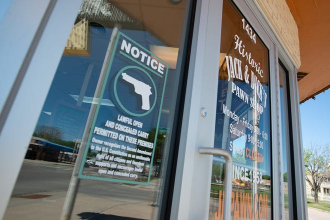 A notice to customers entering Jack and Dick's Pawn Shop in Junction City lets the public know carrying firearms open and concealed is permitted on the property.