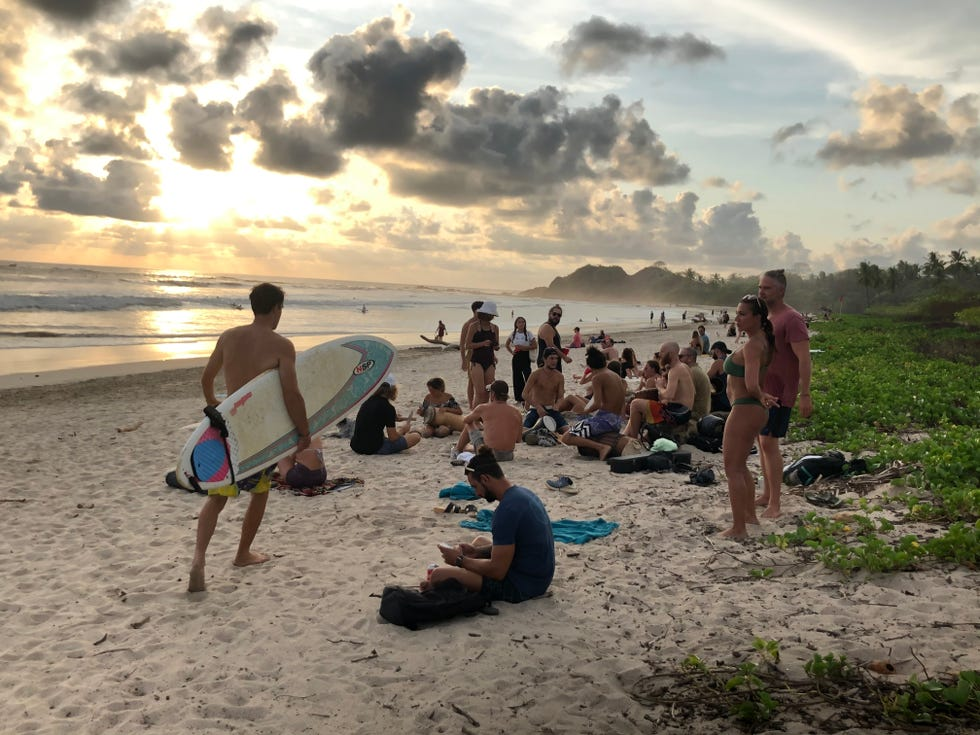 Visitors gather to watch the sunset April 19, 2021, in Playa Guiones, a surfing destination located near the town of Nosara, Costa Rica. Nosara is one area of Costa Rica drawing U.S. travelers, while some others have yet to see a rebound in tourism.