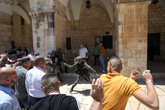 Israeli border police swing their batons at Muslim worshippers to prevent them from gathering for Friday prayers at the Dome of the Rock Mosque in the Al-Aqsa Mosque compound in the Old City of Jerusalem, Friday, May 14, 2021.