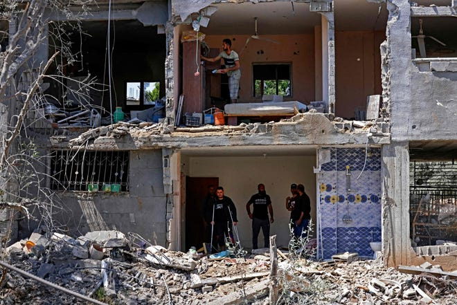 Palestinians assess the damage from an Israeli airstrike to a building in Beit Hanun in the northern Gaza Strip on May 14.