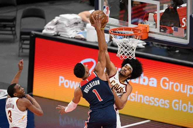 Cleveland Cavaliers center Jarrett Allen, back, blocks a shot by Washington Wizards forward Chandler Hutchison (1) during the second half of an NBA basketball game Friday, May 14, 2021, in Washington. Cavaliers guard Jeremiah Martin is at left. (AP Photo/Nick Wass)