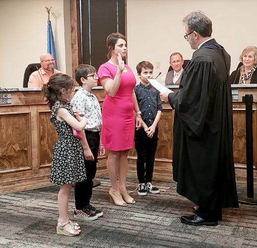 Mayor Beth Glasgow is joined by her children as Judge Thomas Baldwin swears her in during her first term as commissioner in 2019.