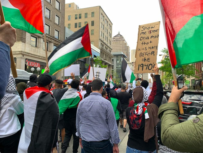 Protesters held signs, chanted and marched down High Street toward Ohio State University Friday evening in support of Palestinians.