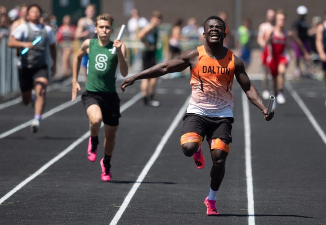Dalton's Adam Knetzer pulls up injured, but still finishes for the 4x100 win.