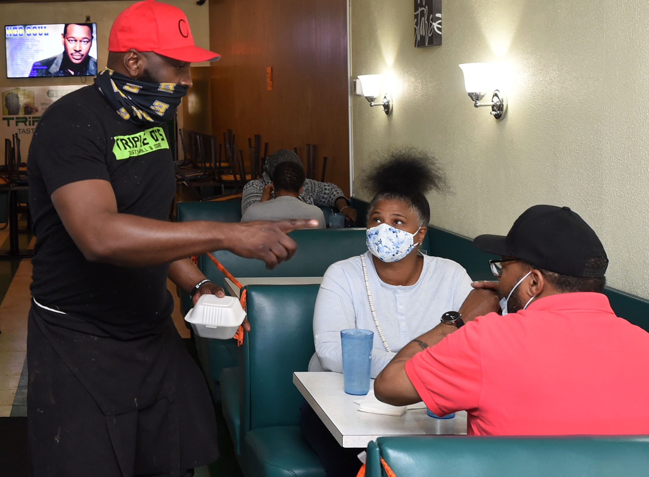 Darrell Roberts, left, owner of Triple D's Tasty Grill, talks with customers Stephanie Nixson and James Warrack, both of Erie, on May 14.