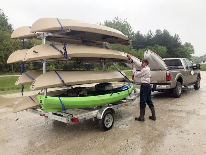 Des Moines County Conservation Director Chris Lee checks canoes and kayaks bound for the first annual Fill the Lake Flotilla Saturday at Big Hollow Recreation Area. An all-morning downpour forced Lee to cancel the event, which will be re-scheduled for sometime in June.