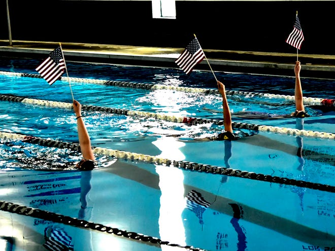 To add to the singing of the National Anthem Thursday at the Western Athletic Conference girls swim meet, members of the Garden City High School team swam the length of the pool in the lanes holding American flags in the air. The WAC meet was held at the Garden City Family YMCA.
