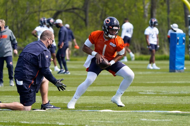 Chicago Bears quarterback Justin Fields (1) looks to hand off the ball during the team's rookie minicamp Friday, May, 14, 2021, in Lake Forest.