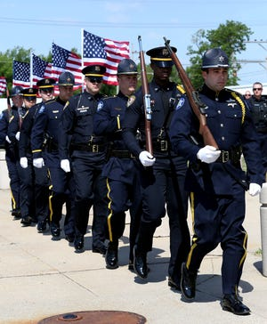 Members of the Reno County Sheriff Dept and the Hutchinson Police Dept color guard march at the beginning of the National Peace Officers Memorial Day ceremony Friday morning in front of the Law Enforcement Center.