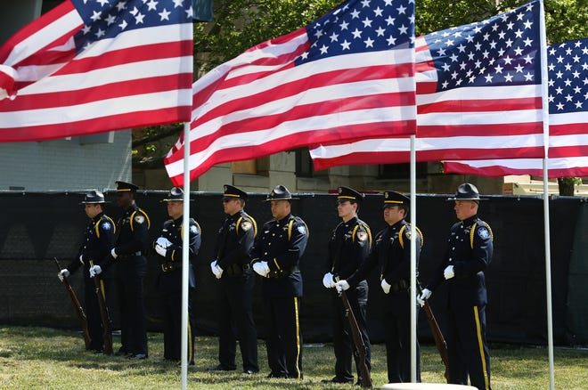 Members of the Reno County Sheriff Dept and the Hutchinson Police Dept color guard stand at parade rest as they wait to raise the American flag during the National Peace Officers Memorial Day ceremony at the Law Enforcement Center Friday.
