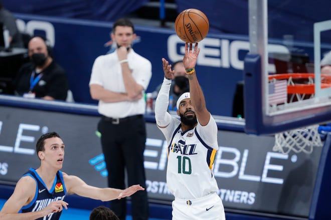 Jazz guard Mike Conley (10) shoots as Thunder forward Aleksej Pokusevski (17) looks on during the first quarter Friday.